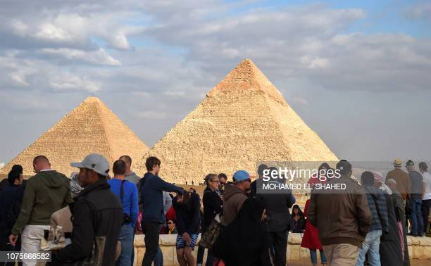 Tourists gather at the Giza pyramids necropolis on the southwestern outskirts of the Egyptian capital Cairo on December 29 with the pyramids of...