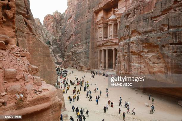Tourists gather in front of the ancient Khaznah monument carved in the rock cliff in Jordan's archaeological city of Petra south of the capital Amman...
