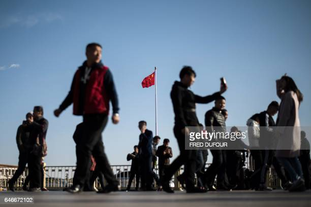 Tourists gather in Tiananmen Square ahead of the upcoming opening sessions of the Chinese People's Political Consultative Conference and the National...