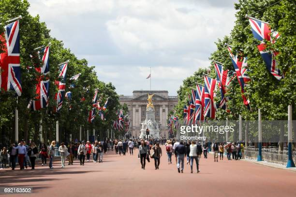 Tourists gather on The Mall, as a Union Flag, also known as the Union Jack, flies at half-mast from Buckingham Palace, the day after a terror attack...