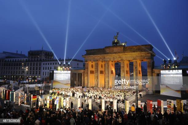 Tourists gather to see the individually painted dominos along the former route of the wall in front of illuminated landmark Brandenburg Gate in...