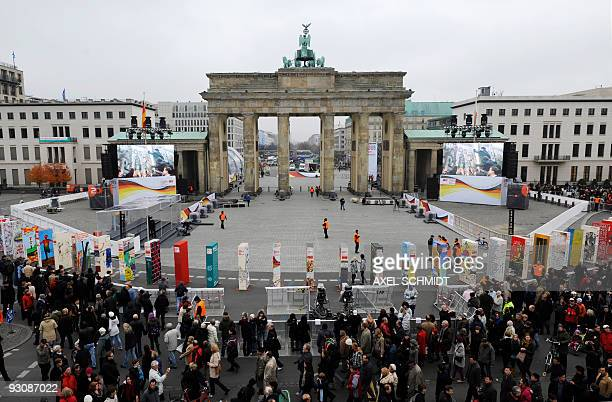 Tourists gather to see the individually painted dominos along the former route of the wall in front of landmark Brandenburg Gate in Berlin on...