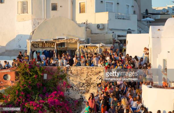 Tourists gather to watch the sun set in Oia village on July 16 2018 in Santorini Greece