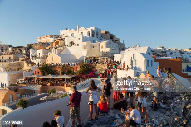 Tourists gather to watch the sun set in Oia village on July 16, 2018 in Santorini, Greece. The Castle of Oia is the most famous place for the sunset...