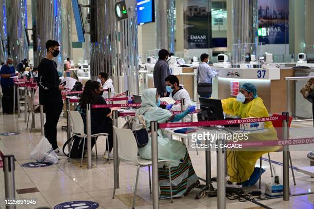 Tourists get a medical screening upon arrival at Teminal 3 at Dubai airport, in the United Arab Emirates, on July 8 as the Gulf emirate reopens to...