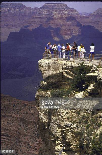 Tourists get breath taking view of Grand Canyon at or near Mather Point with sky bathed in pastel hues of sunrise or sunset
