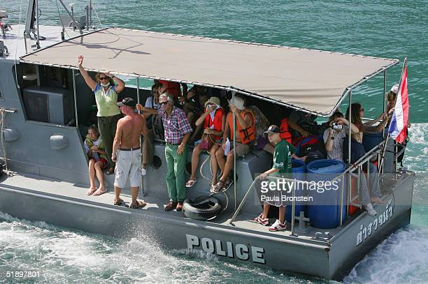Tourists get evacuated on a police boat to Phuket December 28 2004 in Ton Sai Bay Koh Phi Phi Thailand Hundreds were killed when the island was hit...