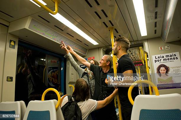 Tourists get help locating their destination on the Metro map from a Portuguese local as they travel on a Metro train in Porto