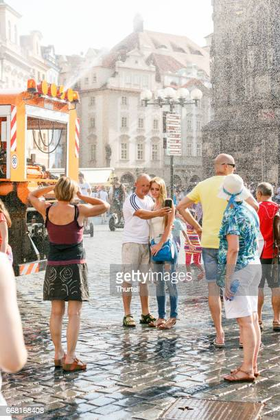 tourists getting relief from summer heat, prague, czech republic - astronomical clock stock pictures, royalty-free photos & images