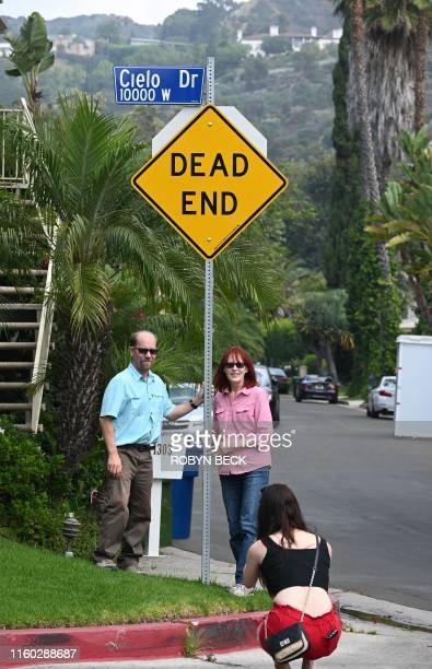 Tourists Glenn Martin and Peggy Miles pose for a photo beside a Cielo Drive street sign during a Dearly Departed Tour related to the Manson Family...