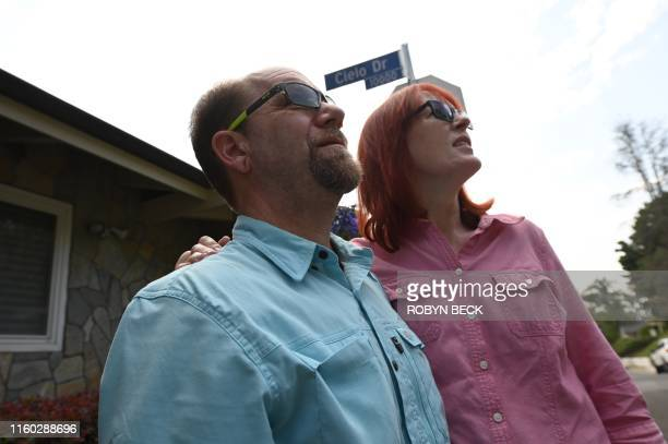 Tourists Glenn Martin and Peggy Miles survey the area on Cielo Drive during a Dearly Departed Tour related to the Manson Family murders in Beverly...