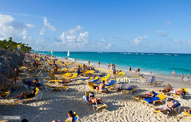 Tourists go for a walk at Bavaro beach in Punta Cana Dominican Republic on January 16 2012 Tourism is the main industry in Dominican Republic and...