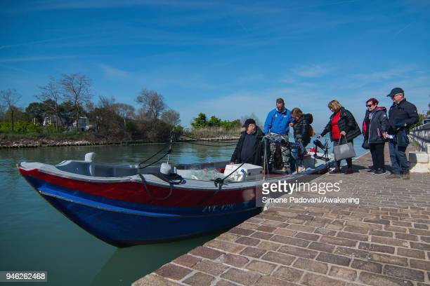 Tourists go in the boat of a tour of fishing tourism of 'Moeche' organized by Cooperativa San Marco in Burano on April 14 2018 in Venice Italy At the...