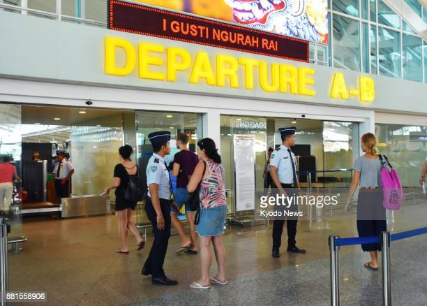 Tourists go through the departure gate at Bali international airport on Nov 29 after Indonesia reopened the airport the same day The airport was...