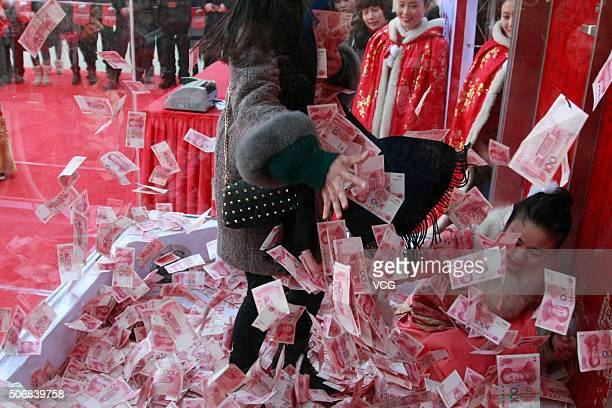 Tourists grab 100yuan banknotes over a blower in the glass house at Song Dynasty Town on January 26 2016 in Hangzhou Zhejiang Province of China Song...