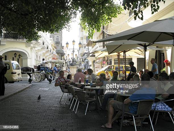 Tourists grab shade and a beverage at a cafe in Parque Colon in the Zona Colonial in Santo Domingo Dominican Republic