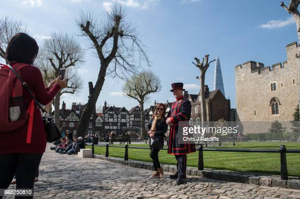 Tourists have photos taken with a Beefeater at the Tower of London on April 6 2017 in London England Predicted temperatures for April are 5 degrees...