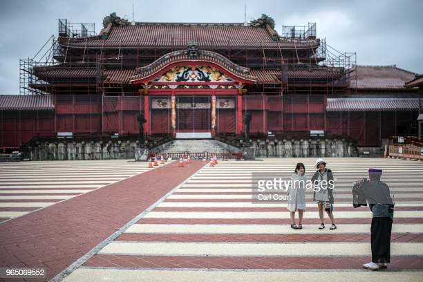 Tourists have their photograph taken by a guide in traditional Okinawan dress as they visit Shuri Castle on June 1 2018 in Naha Japan Like the rest...