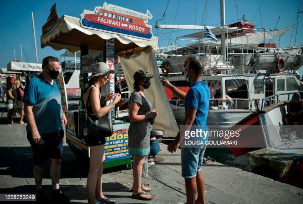 Tourists have their temperature measured prior to boarding a leisure boat taking them to tourist spots on the Aegean island of Rhodes on August 29,...