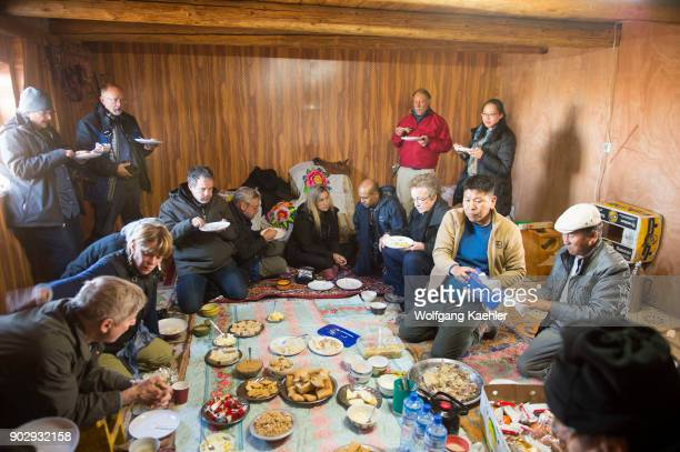 Tourists having a traditional Kazakh lunch in the kitchen of a Kazakh winter camp in the Sagsai Valley in the Altai Mountains near the city of Ulgii...