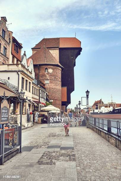 tourists having a walk by medieval port crane by the river motlawa in gdansk - motlawa river stock pictures, royalty-free photos & images