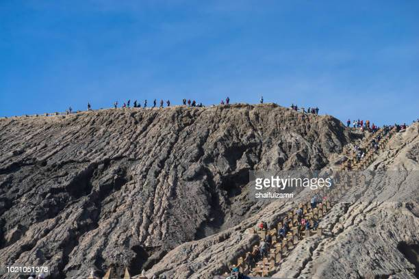 Tourists hiking over beautiful view landscape of active volcano crater with smoke at Mt. Bromo, East Java, Indonesia.