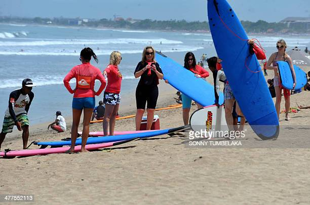 Tourists hold surfboards on Kuta beach in Denpasar on Indonesia's resort island of Bali on March 10 2014 Kuta beach a popular tourist spot will close...