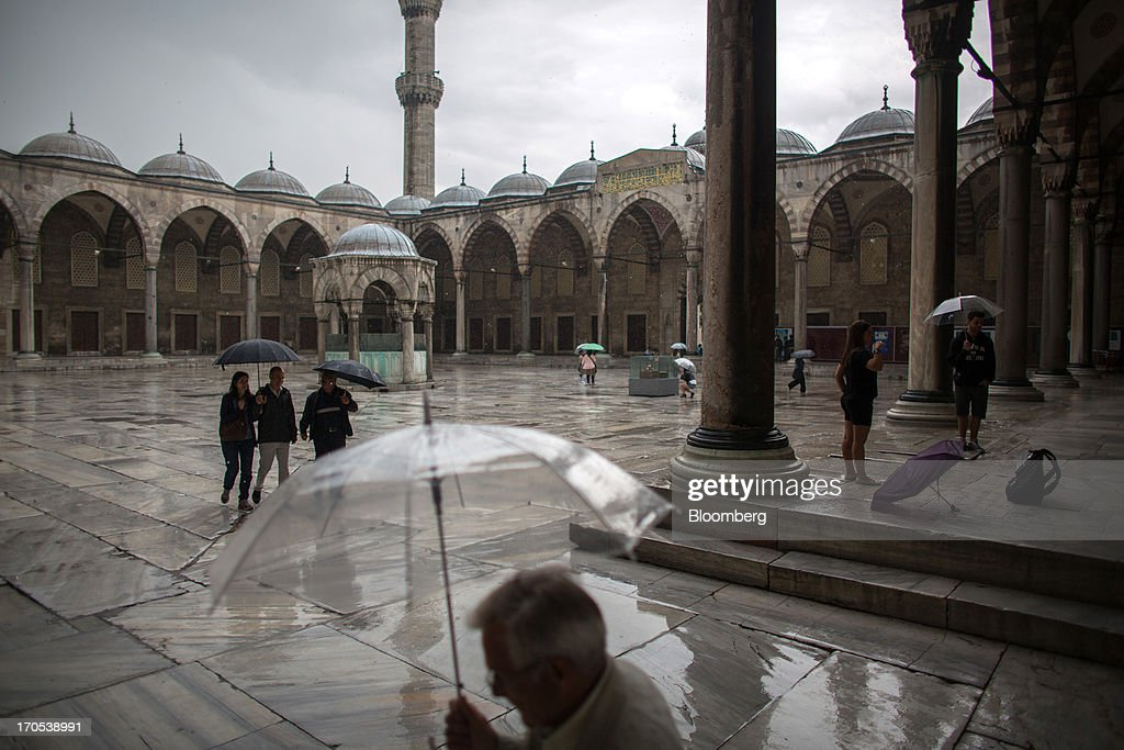 Tourists hold umbrellas to shelter from the rain in the central square inside the Blue Mosque, also known as the Sultan Ahmed, in Istanbul, Turkey, on Friday, June 14, 2013. The law forbids the sale of alcohol at night and near schools and mosques, going against the secular traditions of the Muslim-majority country of 74 million, where many people drink and women often choose not to cover their hair. Photographer: Lam Yik Fei/Bloomberg via Getty Images