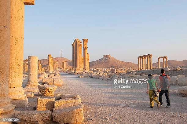 Tourists holding hands in ancient Palmyra, Syria