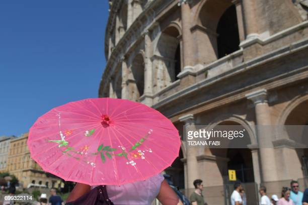 Tourists holds a paper umbrella to protect herself from the sun near the Colosseum on June 21, 2017 in Rome. In Italy, forecasters say the current...