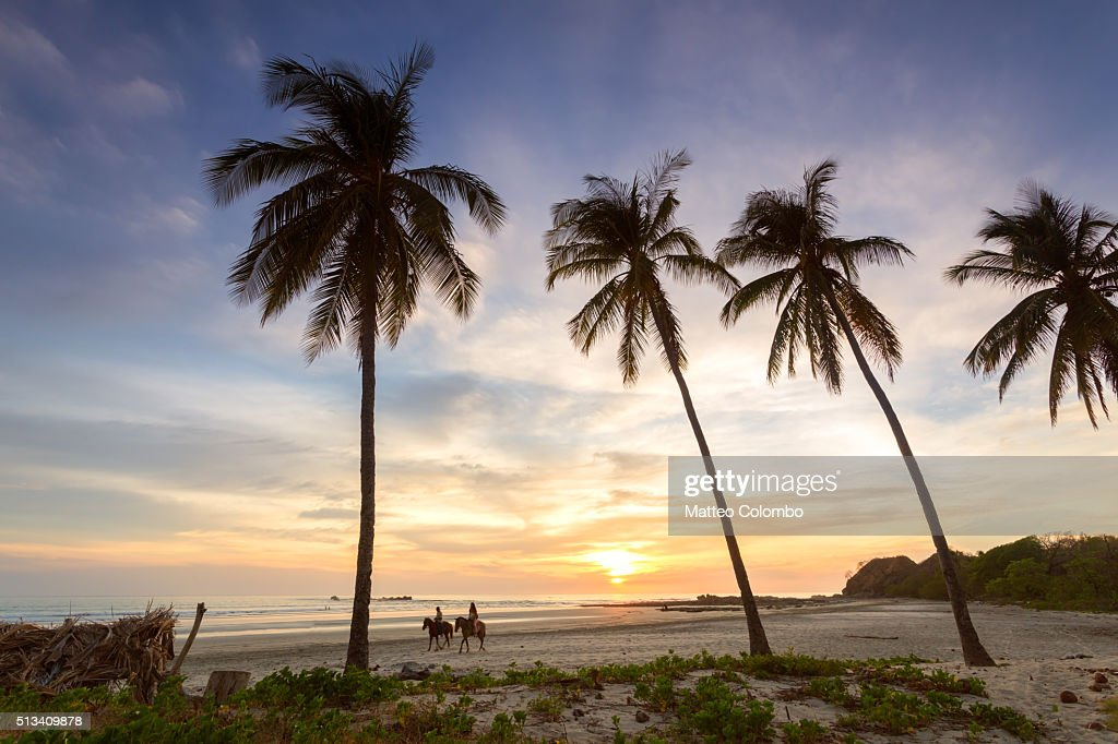 Tourists horse riding on a tropical beach at sunset, Costa Rica : Stockfoto