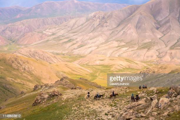 観光客は、山に乗って、湖の歌 kol、キルギスに向かって乗馬 - キルギス ストックフォトと画像
