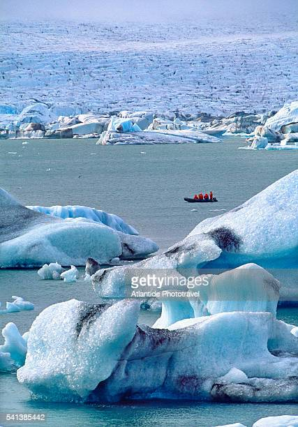 tourists in a boat observe icebergs in the lagoon near vatnajokull glacier - jökulsárlón lagoon stock pictures, royalty-free photos & images