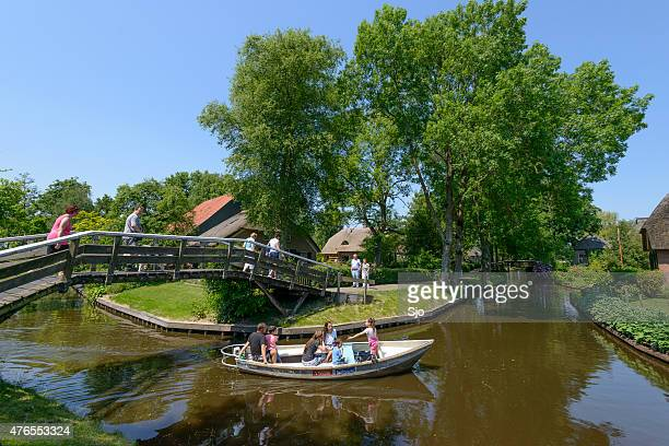 tourists in a boat on the canal in giethoorn - giethoorn stock pictures, royalty-free photos & images