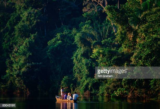 Tourists in a rowing boat with a tour guide on Lake Sandoval Peruvian Rainforest South America
