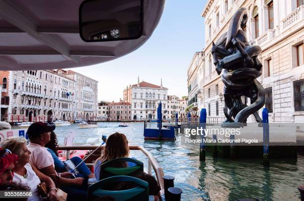 Tourists in a vaporetto looking at Hirst´s sculpture outside Palazzo Grassi.
