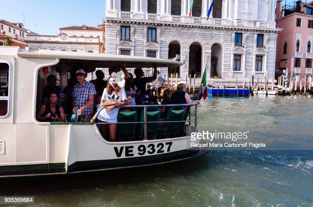 Tourists in a vaporetto on the Grand Canal. Vaporetti are the primary means of transportation.