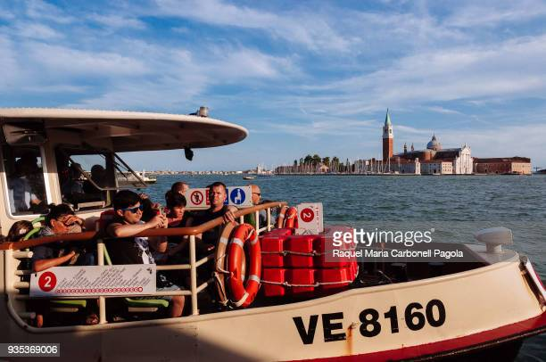 Tourists in a vaporetto sailing on the lagoon with Church of San Giorgio Maggiore at back