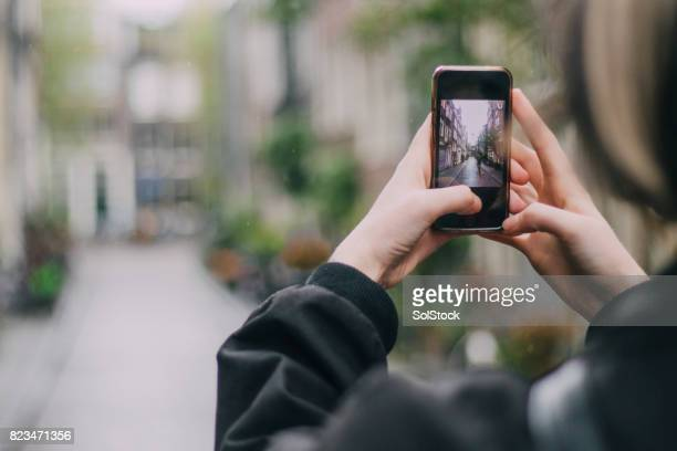 tourists in amsterdam photographing a street scene - photographing stock pictures, royalty-free photos & images