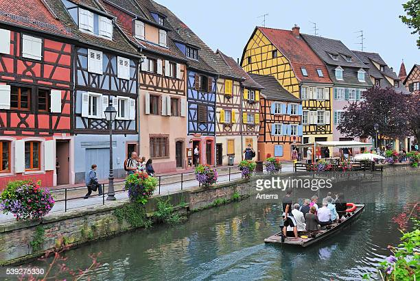 Tourists in boat during sightseeing trip along the colorful facades of timber framed houses at Petite Venise / Little Venice Colmar Alsace France