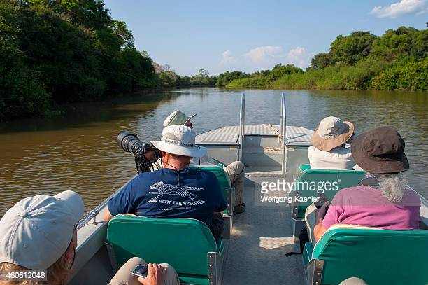 Tourists in boat exploring the Pixaim River in the northern Pantanal Mato Grosso province of Brazil