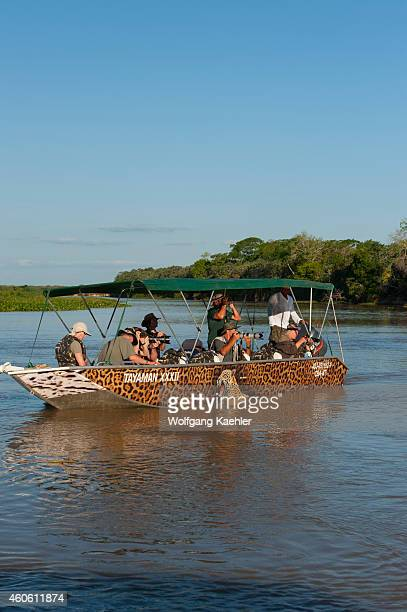 Tourists in boat on excursion to watch and photograph the wildlife in one of the tributaries of the Cuiaba River near Porto Jofre in the northern...
