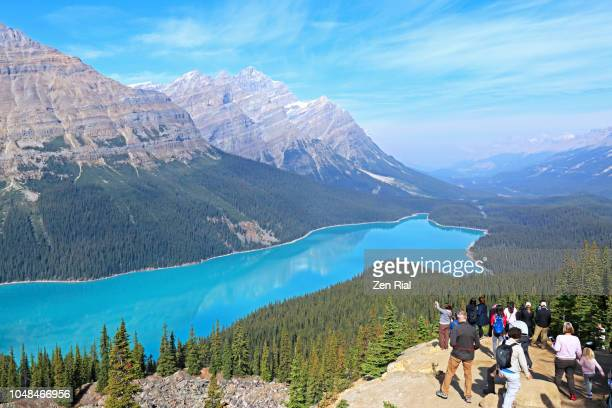 tourists in bow summit viewing peyto lake and impressive mountains of the canadian rockies - banff national park stock pictures, royalty-free photos & images