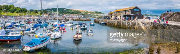 tourists in busy lyme regis harbour marina panorama dorset uk - ilfracombe stock pictures, royalty-free photos & images