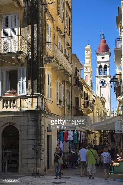 Tourists in by Spianada and Church of Saint Spyridon clock belltower in Agiou Spiridonos Kerkyra Corfu Town Greece