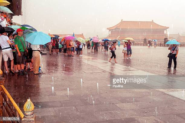 tourists in forbidden city, storm, beijing, china - pavliha stock photos and pictures