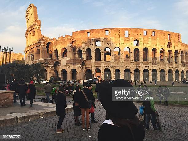 Tourists In Front Of Coliseum Against Sky