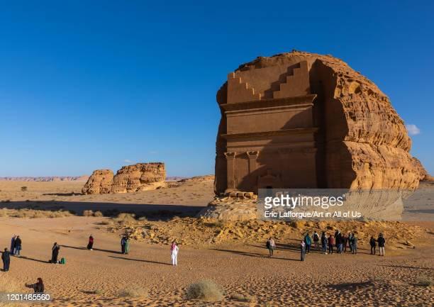 Tourists in front of qasr al-farid tomb of Lihyan son of Kuza in Madain Saleh, Al Madinah Province, Alula, Saudi Arabia on December 27, 2019 in...