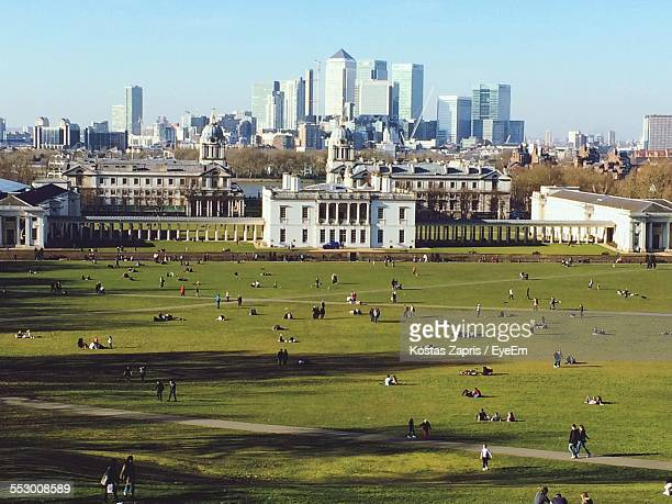 tourists in greenwich park with canary wharf in background - greenwich london stock pictures, royalty-free photos & images