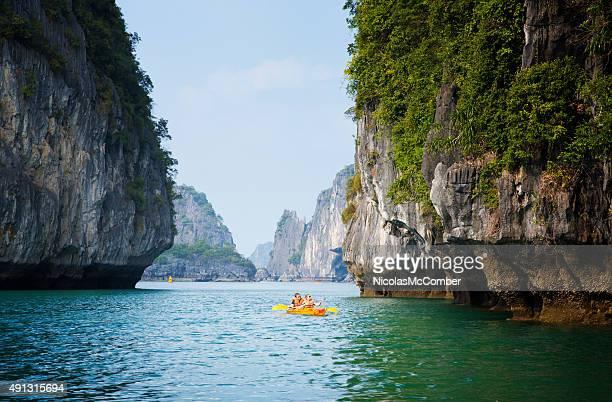Tourists in Halong Bay Vietnam using selfie stick on kayak